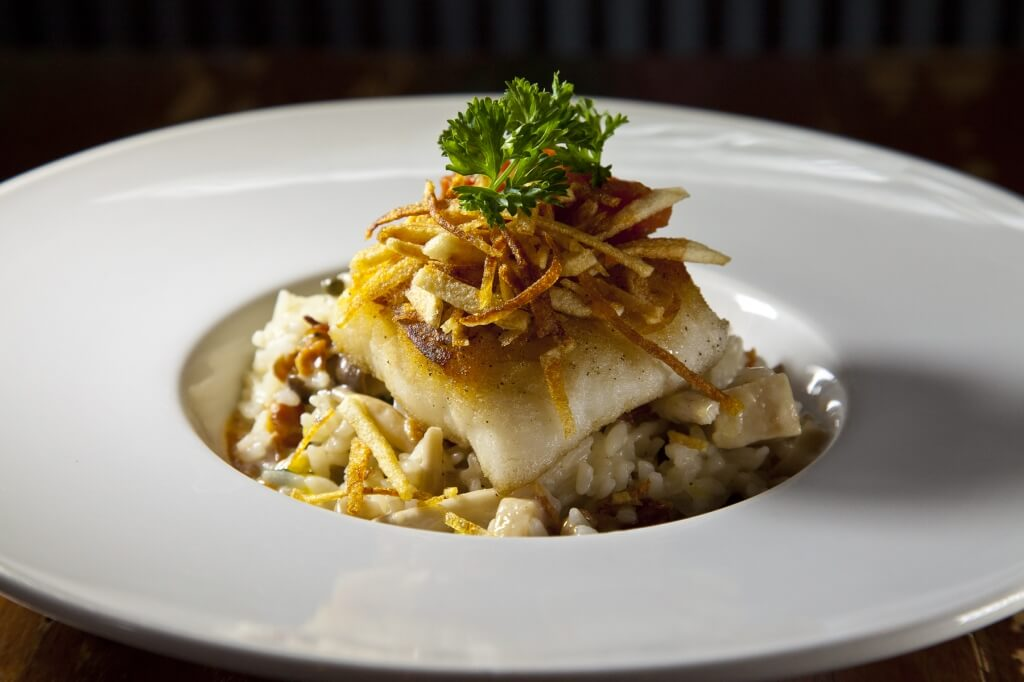 Baked Cod served on a bed of mushroom sushi rice risotto in bacon champagne sauce topped with tomatoes fondue and pommes frites