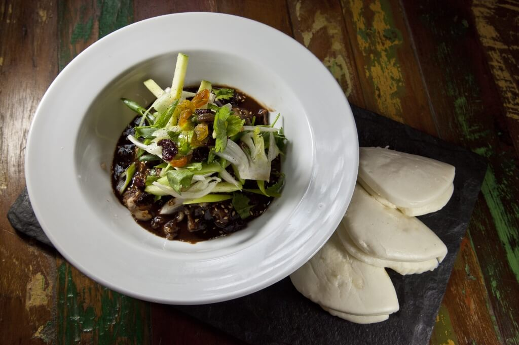 Braised pork belly served in a five spice rich mole sauce topped with shaved fennel, apple, raisins, and cranberry salad