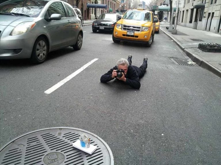 Battman lying in the street taking pictures for the Street Eats book.